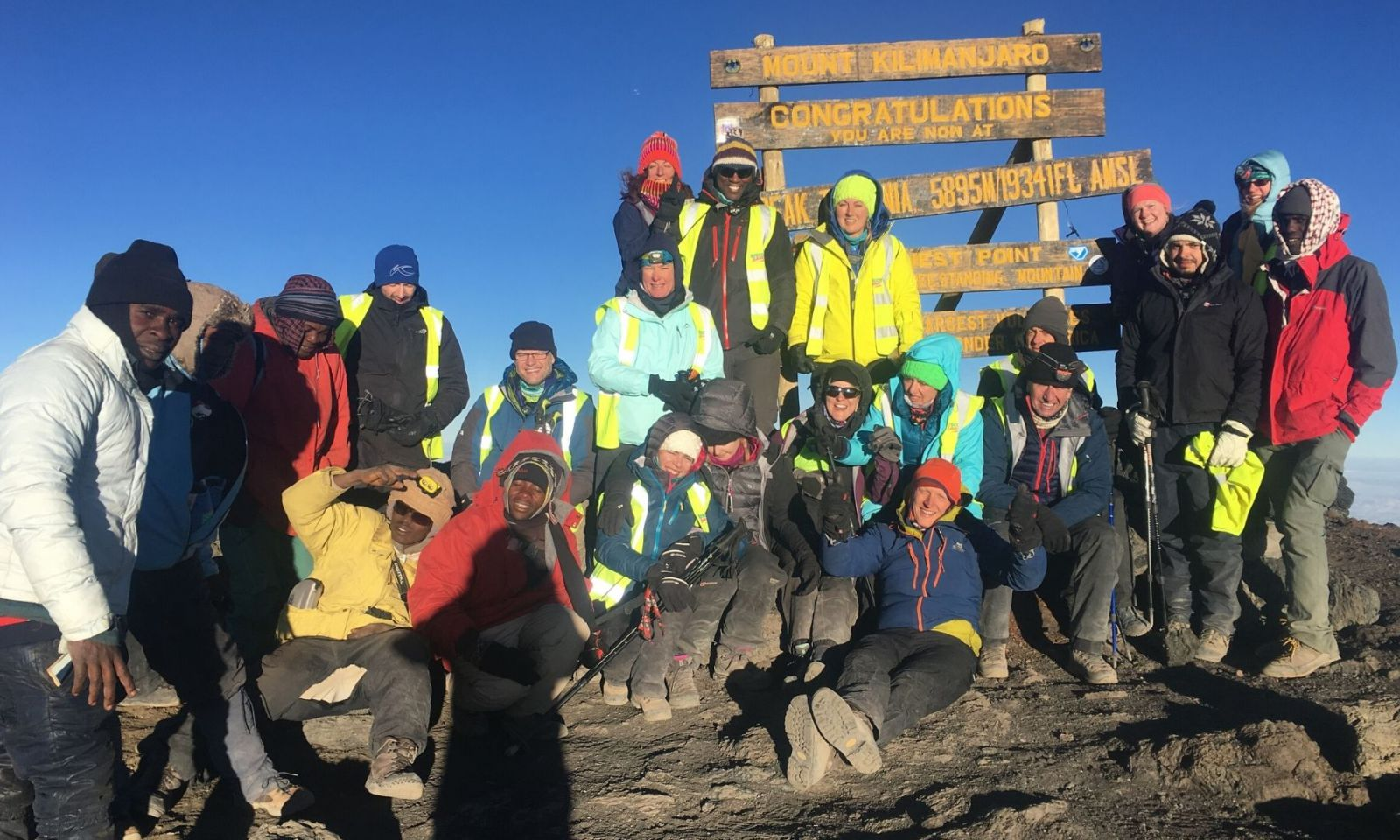 Group of trekkers standing on the summit of Kilimanjaro.