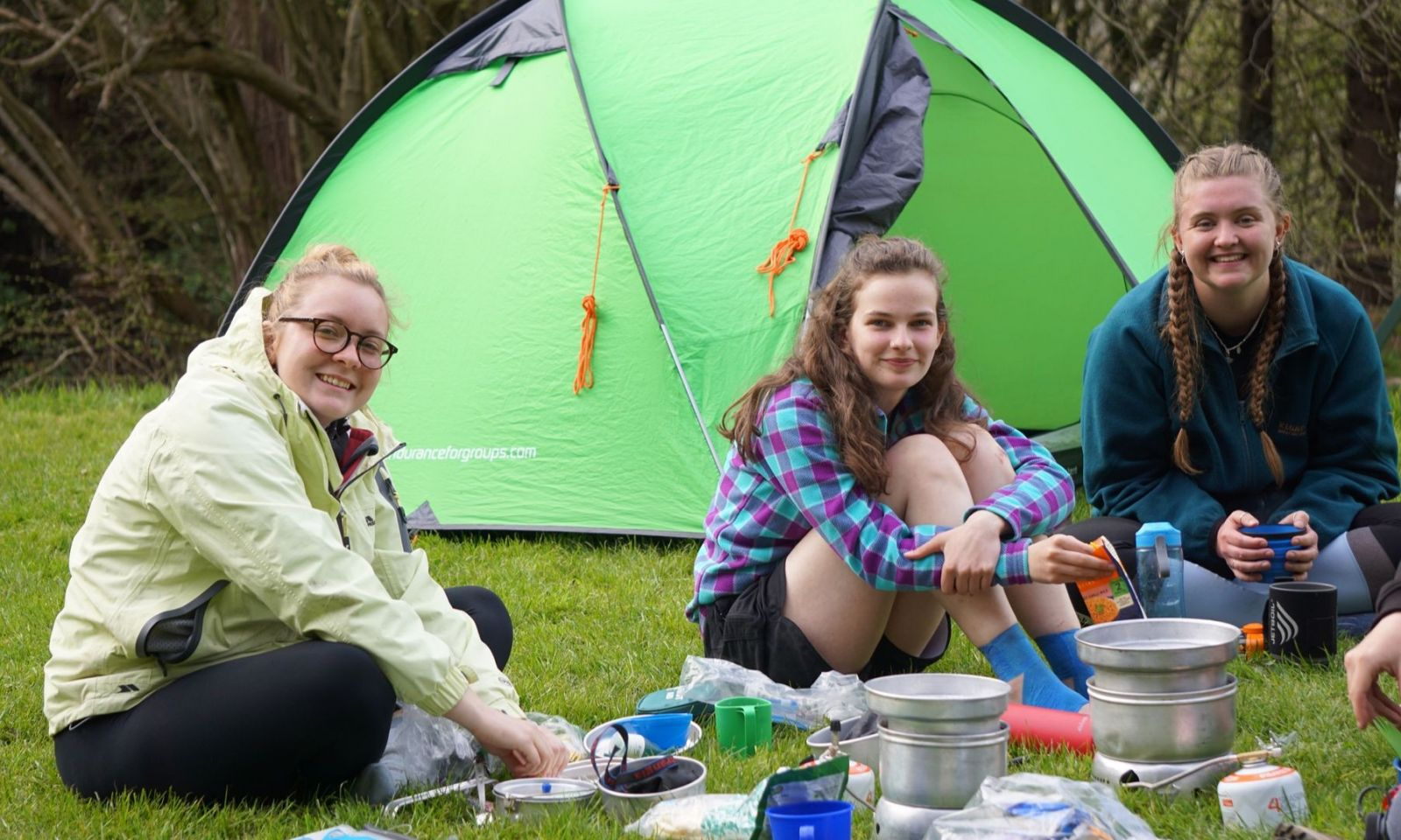 Group of girls smiling as they cook dinner on their stoves during a DofE expedition.
