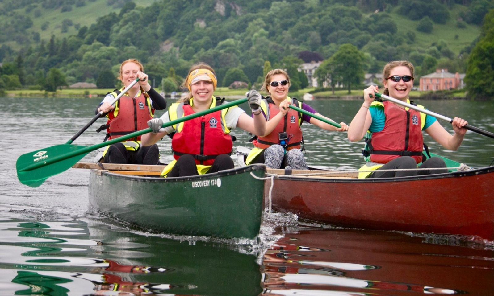 4 people in canoes smiling and having fun on the lake.