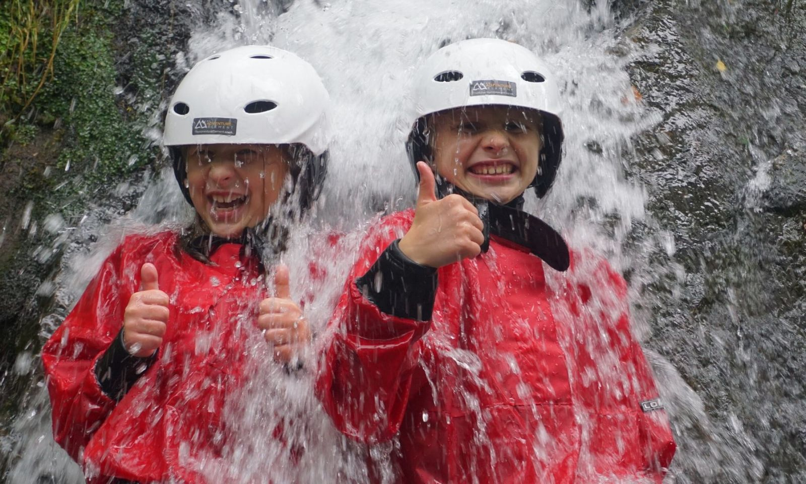 2 young boys lying in a waterfall with their thumbs up and laughing on a Ghyll scramble.