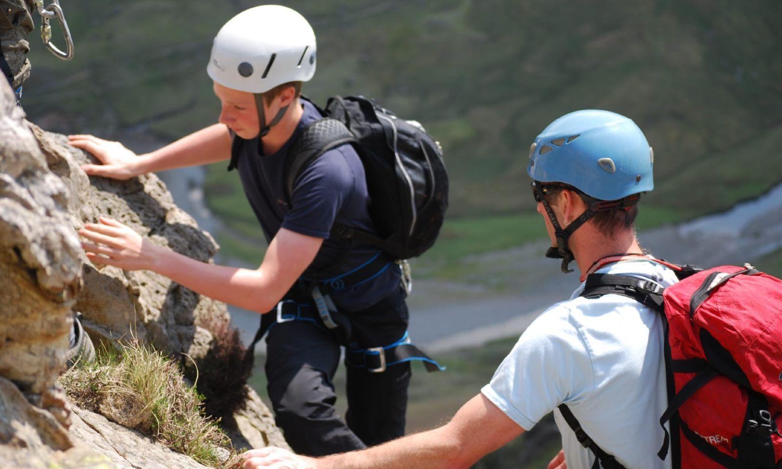 Young boy and an instructor enjoying climbing.