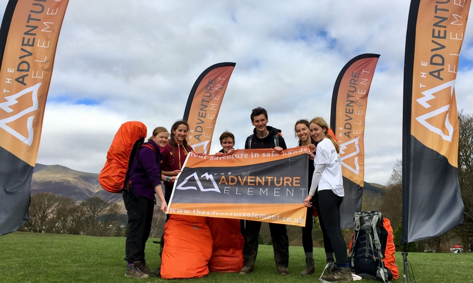 Team smiling and looking happy holding company flag after completing their DofE expedition.