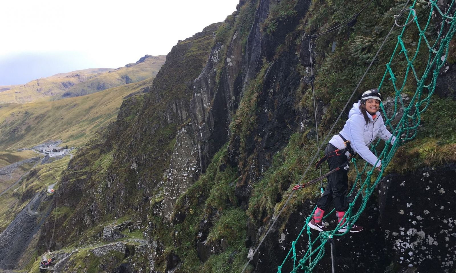 Girl climbing a rope net on the Via Ferrata at Honister Slate Mine.
