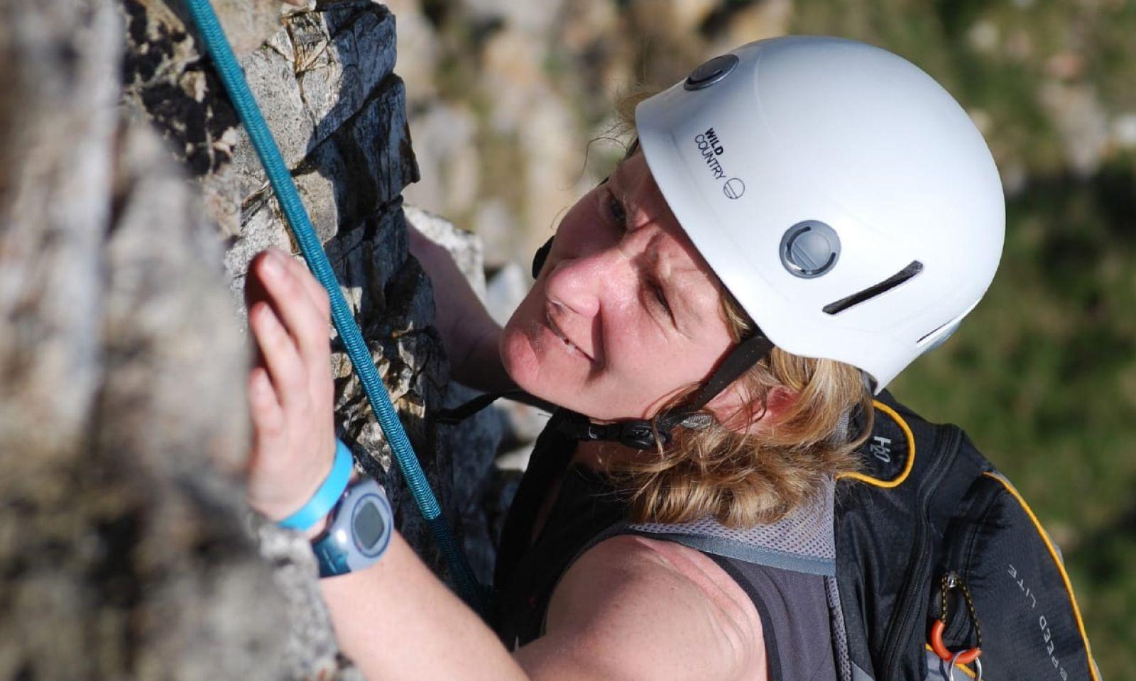 Lady wearing white climbing helmet climbing on rock