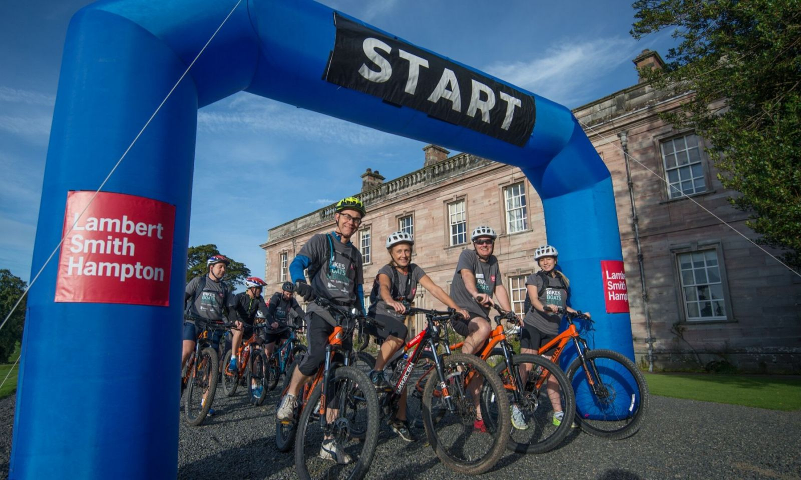 Cyclists grouped together under the start arch before a challenge event.