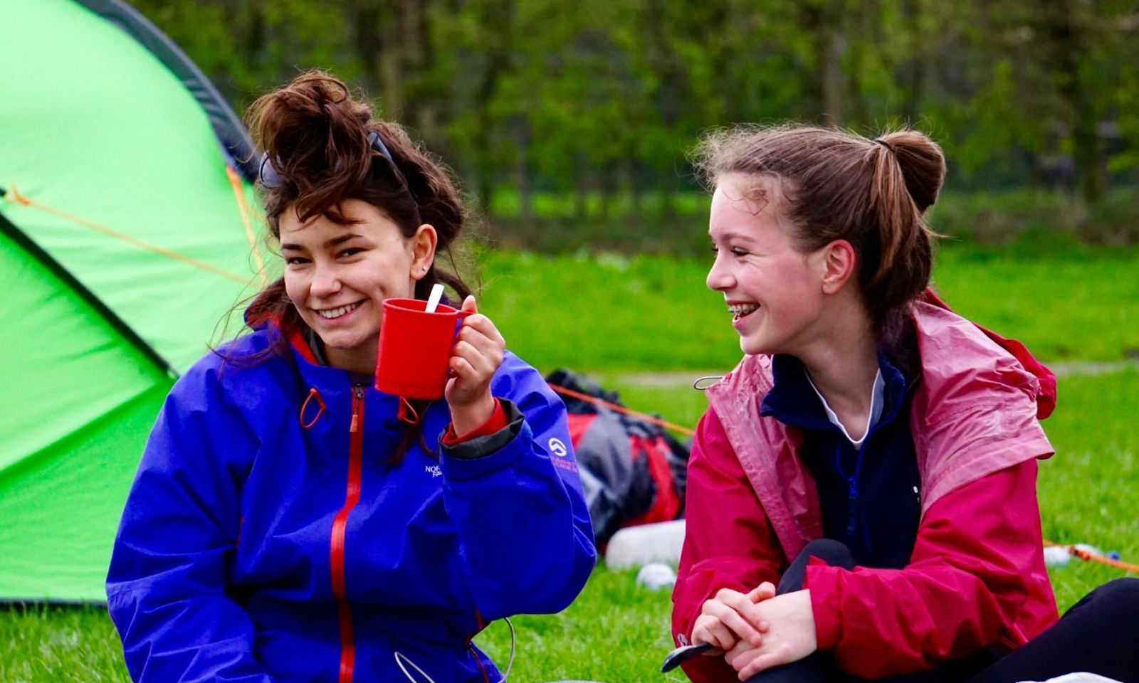 2 girls on their DofE expedition smiling and having fun.