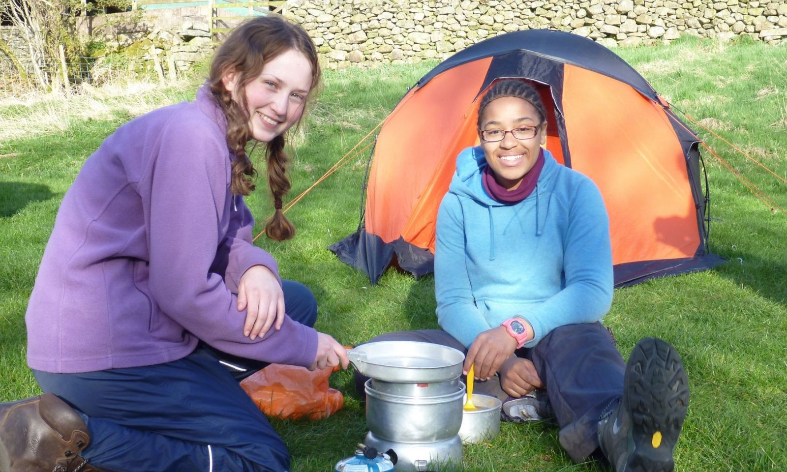2 girls smiling and enjoying cooking on their stove during a DofE expedition.