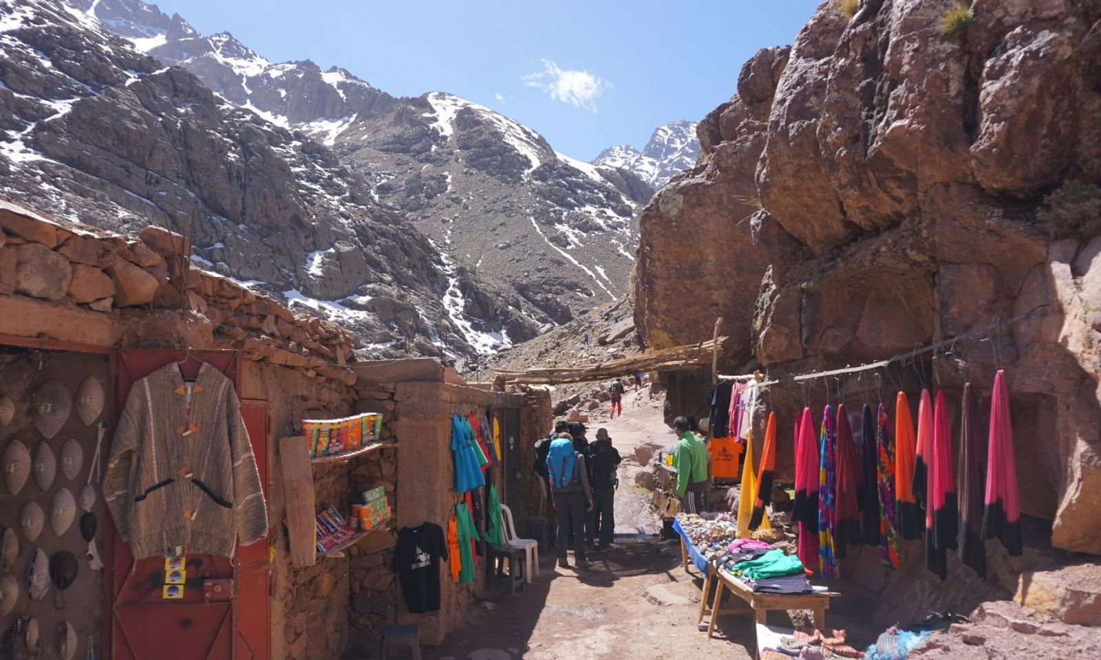Group walking in the Atlas mountains beside shop.