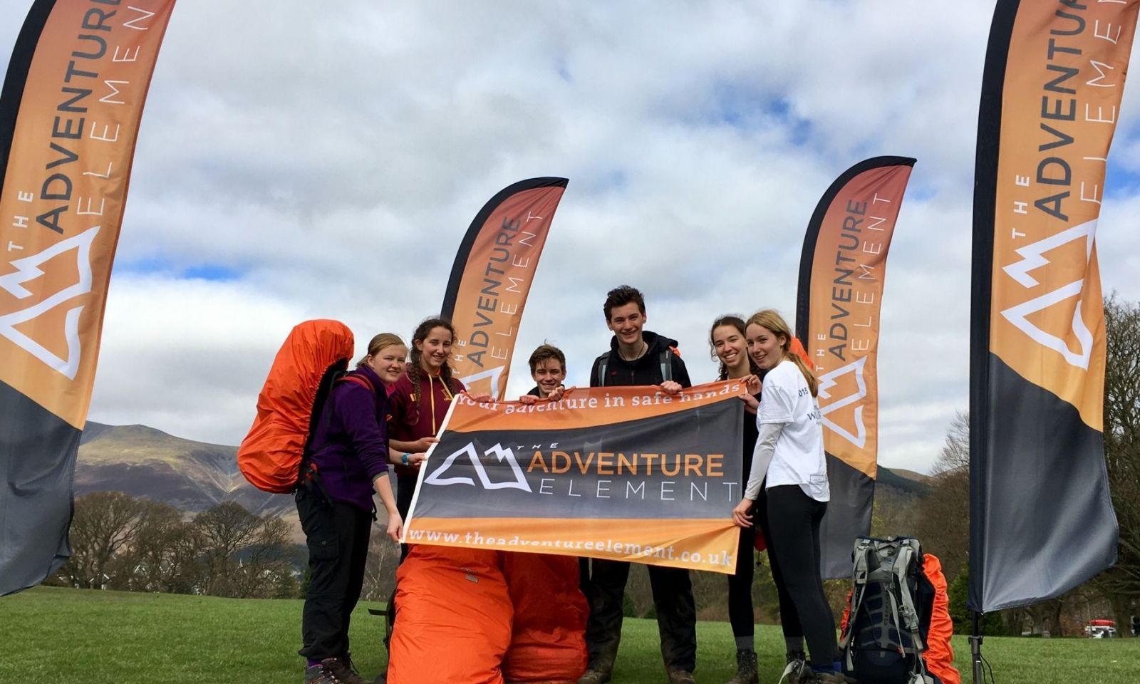 Group of DofE participants stand in front company flag and holding The Adventure Element flag.