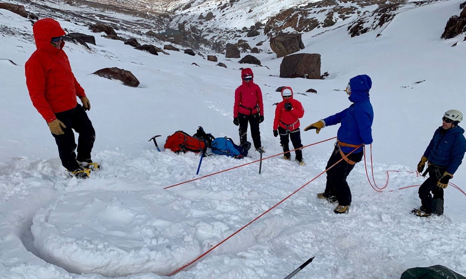 Group getting instruction n the use of a rope on a winter skills course